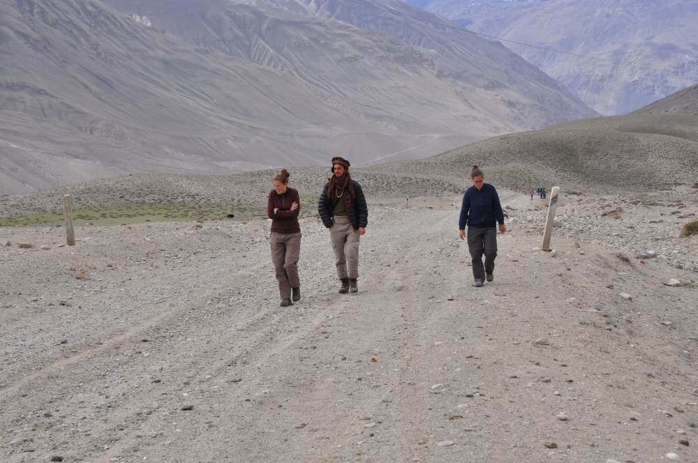 Drei Leute laufen Berg hinauf
