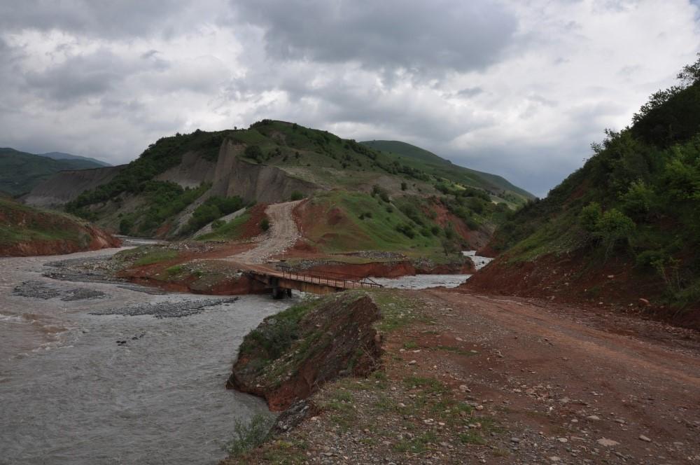 Rötliche Hügel am Fluss mit Brücke