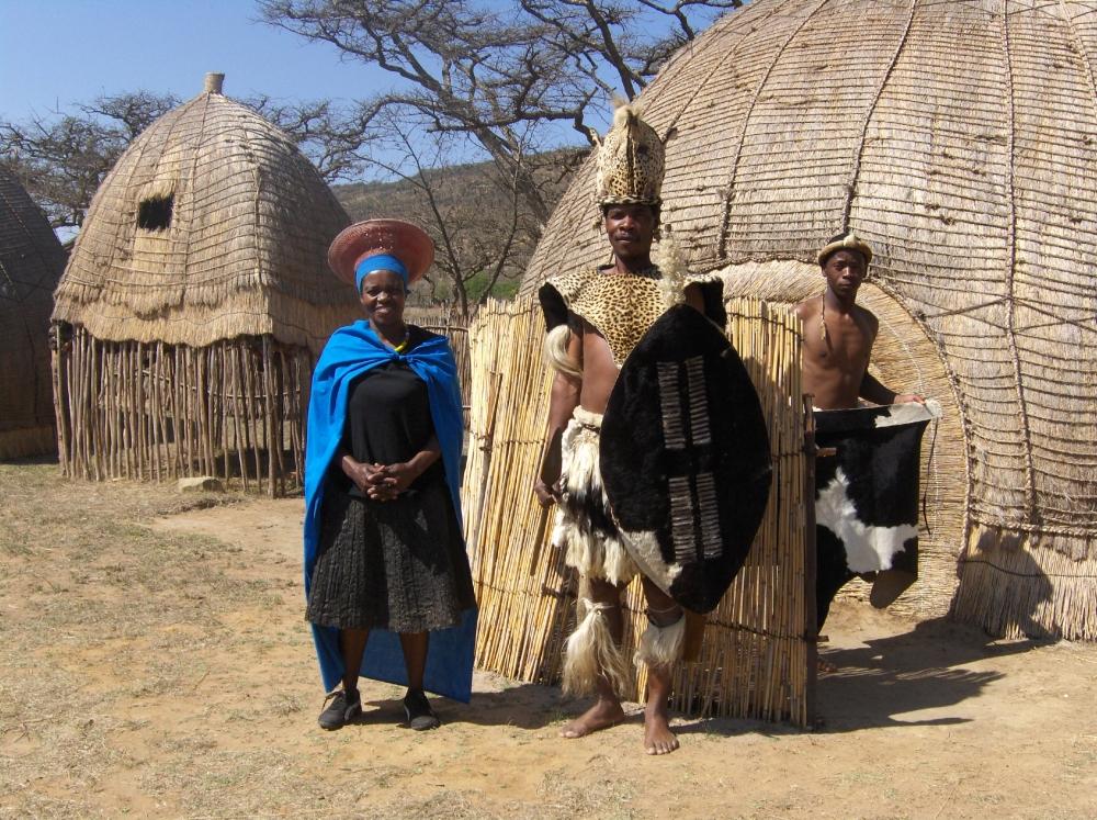 Zulu-Krieger und seine Frau vor der Rundhütte