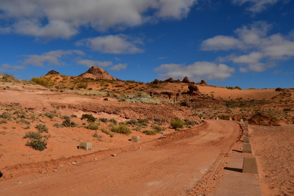 Roetlicher Sand entlang der Piste