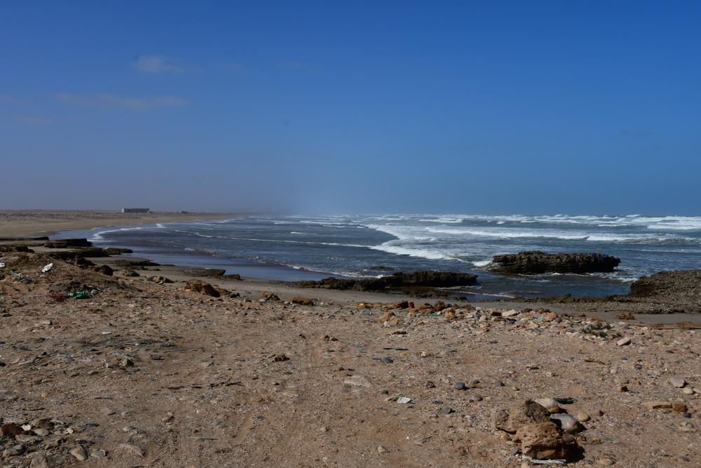 flacher Steinstrand Muell Wellen Atlantik