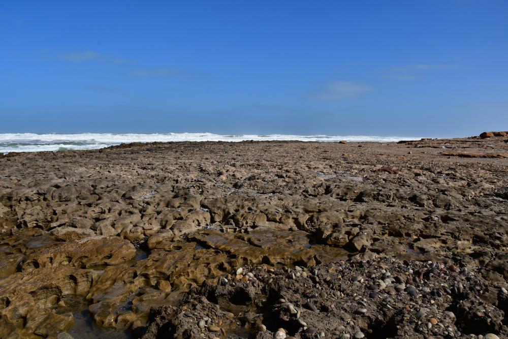 zerfurchte flache Felsen Strand Welle