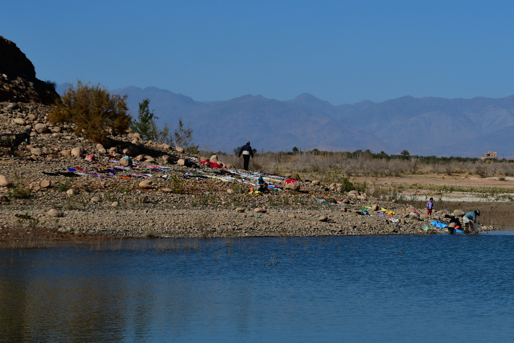 Familie waescht Kleider am Stausee bei Ouarzazate