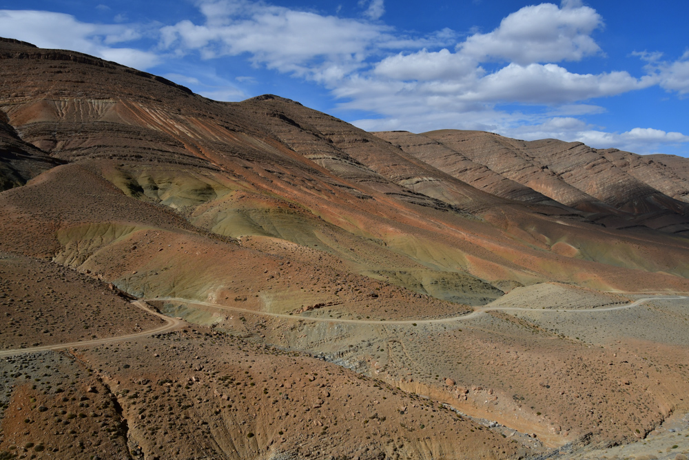 Passstrasse gruen roetliche Berge mit Streifen