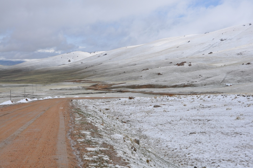 Matschige Strasse entlang beschneiten Hügeln