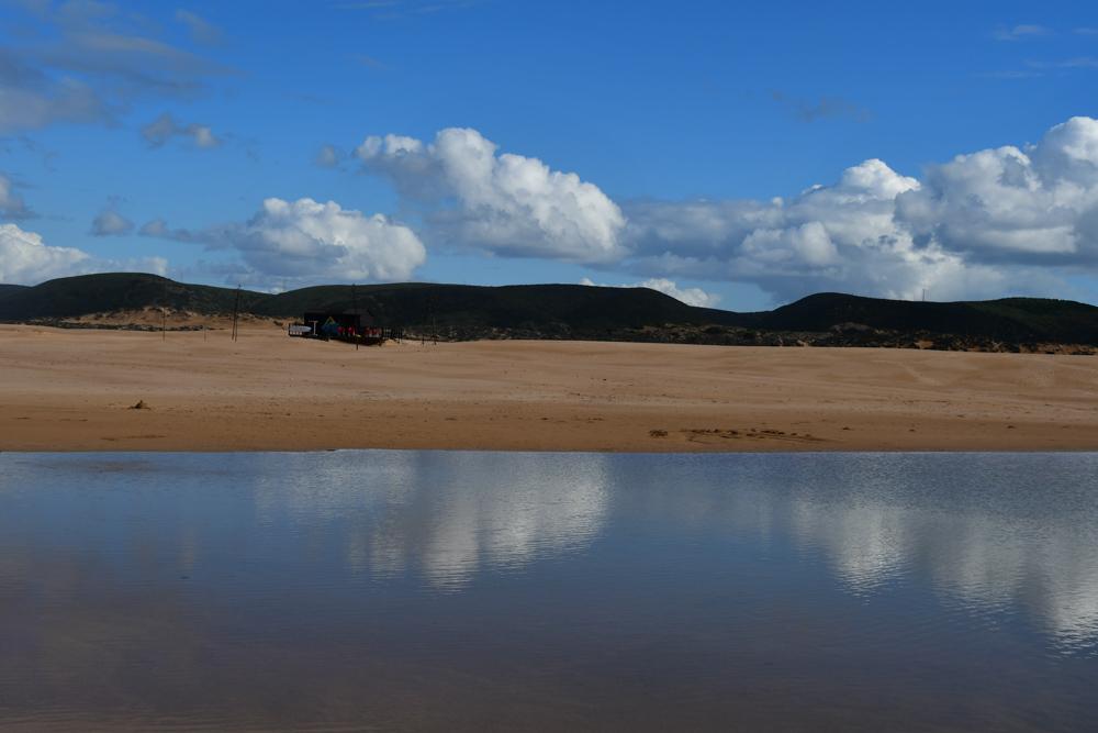 Wasser am Sandstrand gruene Huegel