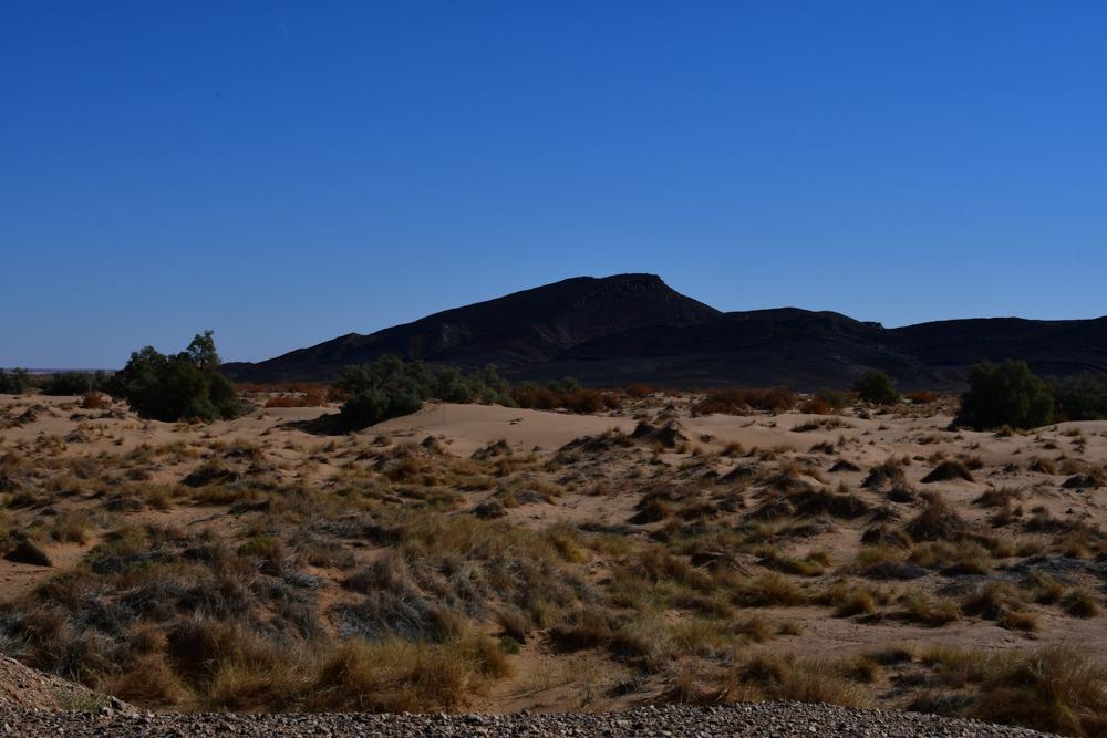 Dunkler Berg vor sandiger Landschaft Bueschel